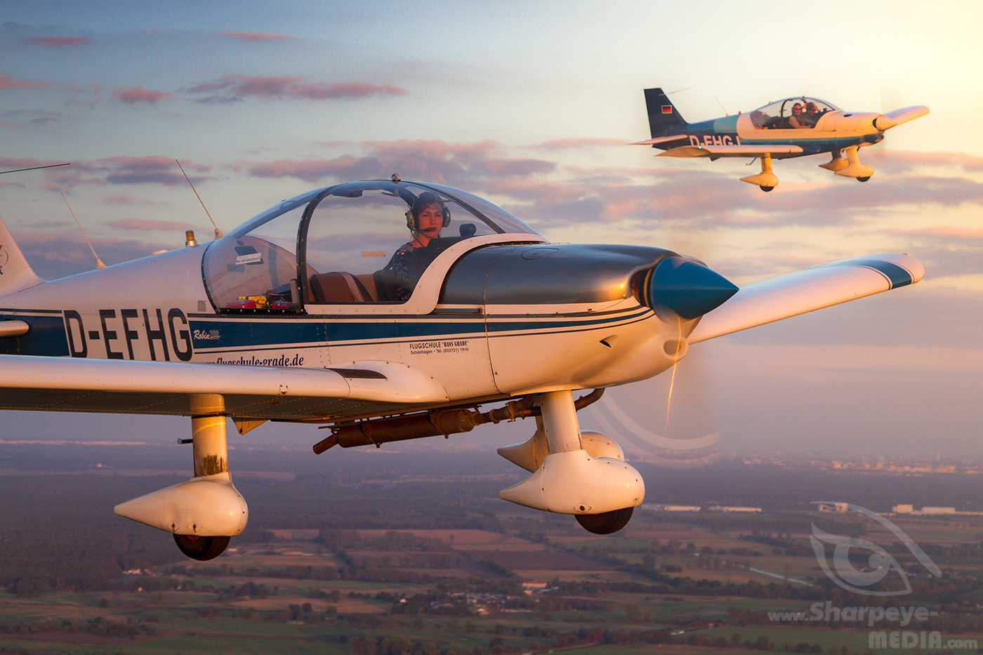 Two Robin Dr-200 aircraft of flyingschool Hans Grade in beautiful evening light in the sky above germany