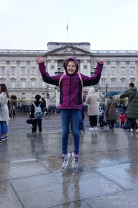 girl jumping in front of buckingham palace london