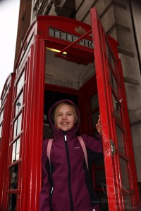 girl in a typical red call box in london