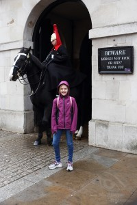 girl posing in front of a mounted trooper in london