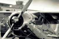 silver polished cessna 195 in front of hangar 2